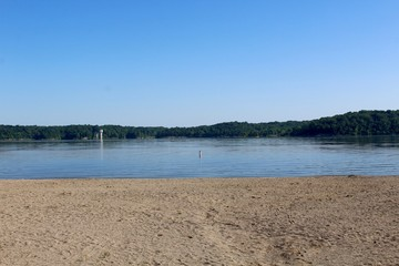 The view of the lake from the waters edge on the beach.
