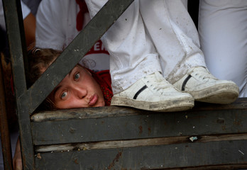 A reveler looks through the barrier before the second running of the bulls at the San Fermin festival in Pamplona
