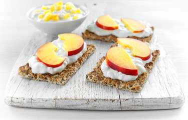 Homemade Crispbread toast with Cottage Cheese and nectarine on white wooden board.