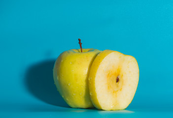 closeup, yellow Apple on a blue background.