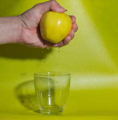 hand with yellow Apple, falling drops in a glass of water.