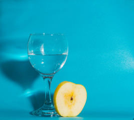 on a blue background and a slice of yellow Apple with a glass of water.