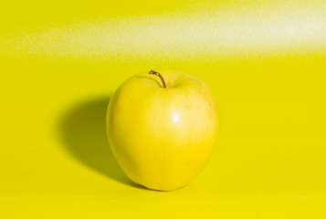yellow Apple on green background, closeup.