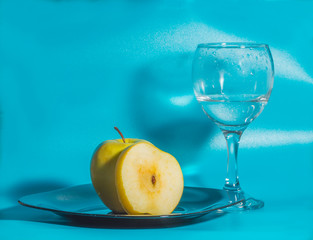 yellow Apple in the plate with a glass of water on a blue background.