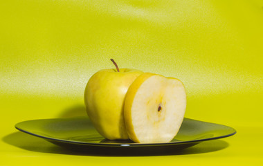 yellow Apple on a plate on a green background.