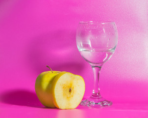 yellow Apple with a glass of water on a pink background.