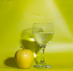a glass of water and a yellow Apple on a green background.