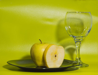 a glass of water and yellow Apple on plate on green background.