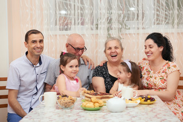 big family drinking tea in dining room