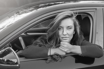 Black and white portrait of young attractive Caucasian business lady with long hair wearing formal suit posing on the wheel of red modern car smiling gently and looking deeply with beautiful eyes.