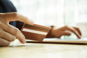 Close-up image of asian business man hands holding credit card and using digital tablet smart phone.Paying with credit card when shopping online. Online shopping concept