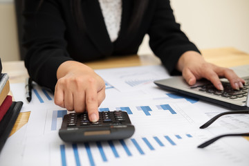 Close up asian Business woman using a calculator to calculate the numbers.Business finances and accounting concept
