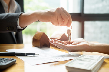 real estate agent holding house key to his client after signing contract,concept for real estate, moving home or renting property