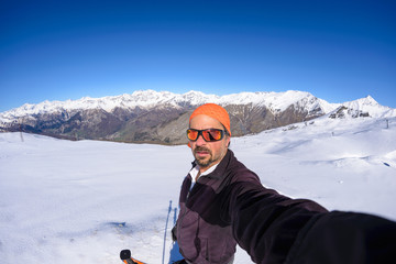 Adult alpin skier with beard, sunglasses and hat, taking selfie on snowy slope in the beautiful italian Alps with clear blue sky. Concept of wanderlust and adventures on the mountain.
