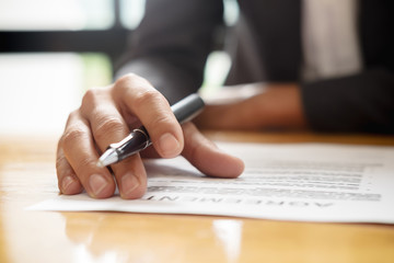 Hand of businessman in suit filling and signing contract,have a contract in place to protect it,signing of partnership agreement form clipped to pad closeup in office.