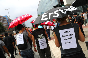 People hold umbrellas and banners during demonstrations at the G20 summit in Hamburg