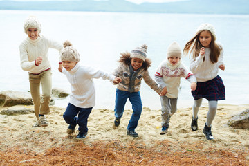 Group of happy children playing outdoors running on lake shore on warm autumn day all dressed in similar knit clothes