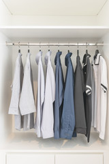 clothes hanging on rail in wooden white wardrobe
