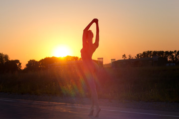 Attractive young fit girl meditates and dances on the empty road at sunset