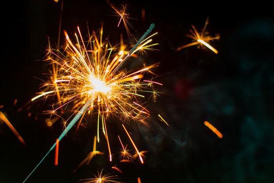 Warm colored sparkler with dark background