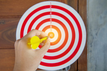 Close up of hand of businessman holding the arrow with number and dart at the target business.