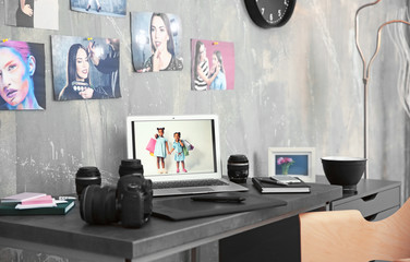 Photographer work space with laptop, graphics tablet, camera and lenses