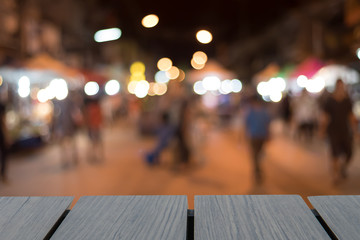 Dark wooden table on font and night street market. blurred background. text show