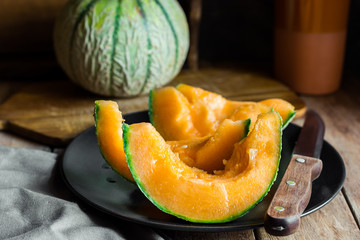 Whole and sliced ripe organic cantaloupe with juicy orange pulp, dark plate, knife, wood cutting board, rustic kitchen interior, cozy atmosphere