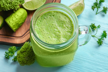 Mason jar with fresh green smoothie on wooden table