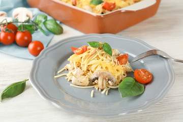 Plate with delicious roasted turkey tetrazzini on wooden table
