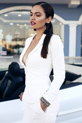 sensual woman with dark hair posing in luxurious car