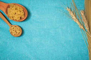 Pasta in wooden spoons,  spaghetti and wheat on a blue background.