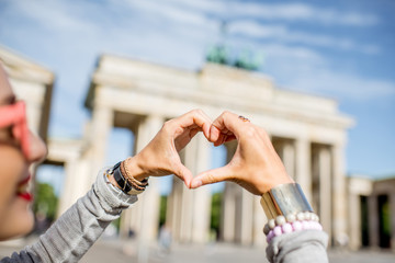 Aluminium Prints Berlin Young woman tourist making heart shape with hands in front of the famous Brandenburg gates in Berlin