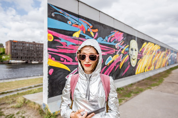 Portrait of a young woman tourist standing in front of the Berlin wall in Germany