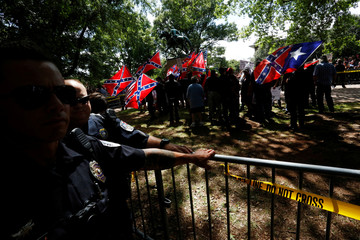 Riot police protect members of the Ku Klux Klan from counter-protesters as they arrive to rally in opposition to city proposals to remove or make changes Confederate monuments in Charlottesville, Virginia
