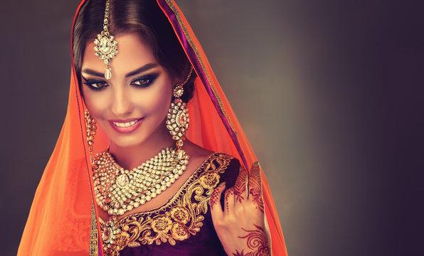 Portrait of beautiful indian girl. Young hindu woman model with golden kundan jewelry set . Traditional Indian costume lehenga choli .