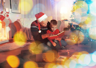 Elderly man with grandson reading book in living room decorated for Christmas