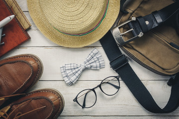 Top view accessoires to travel with man clothing concept.essential items for trip are bow tie on wooden background.watch,eyeglasses,bag,hat,airplane,map on white wood table.flat lay.Above view.