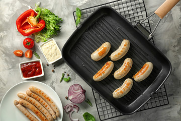 Composition with delicious grilled sausages on kitchen table