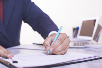 Close-up view of a businessman's hands writing on white paper. Two computers on the table.