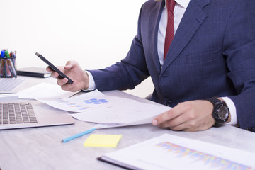Businessman holding a smartphone. Close up view of a young businessman working on his desk white background. Man looking at paper charts and at laptop screen.