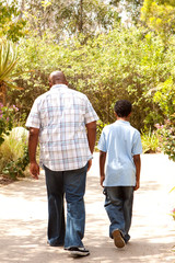Rear view of an African American father and son taking a walk.