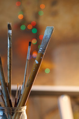 Brushes on the background of paintings in the artist's studio