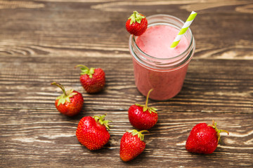 Healthy strawberry smoothie in mug on rustic wood