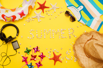 summer beach set: rubber ring, sunglasses, hat, player and earphones, seashells and starfish on a yellow background