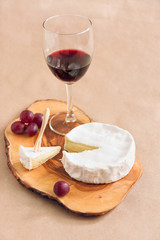 Camembert cheese, grapes and a glass of red wine