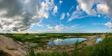 Green fields and ponds under blue sky with clouds. Nature landscape PANORAMA.