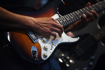 Man's hands playing on an electric guitar in a band on stage, entertainment of a guitarist artist with his music instrument
