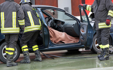 Firefighter team extracts the person from inside the car after a