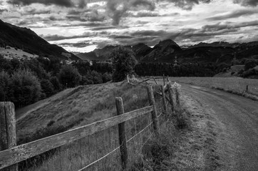 Small rural road and old wooden fence in the countryside near Axams Austria